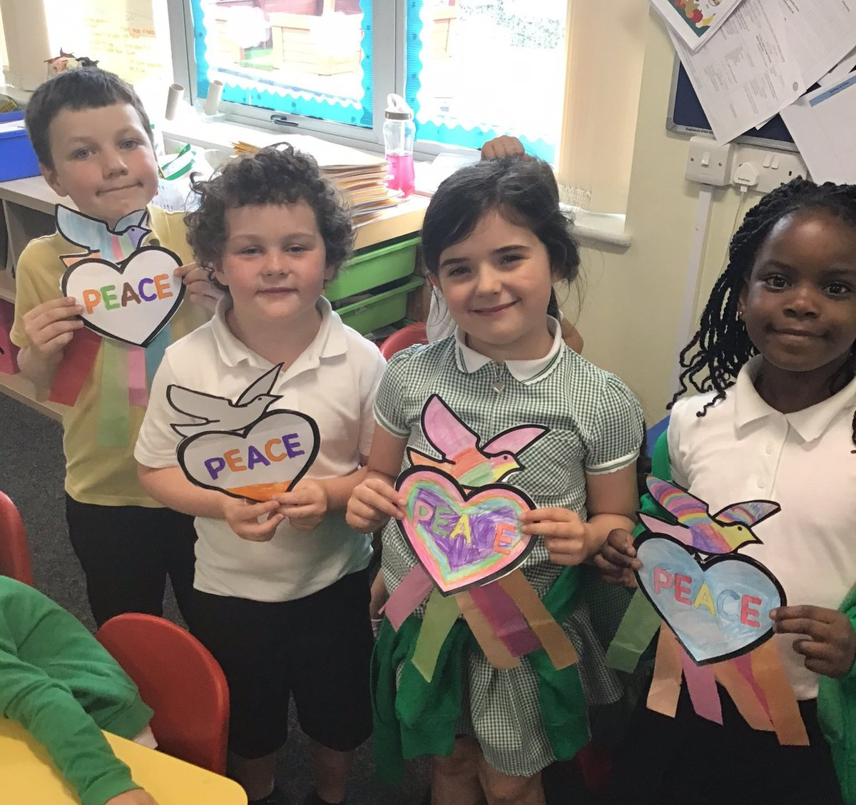 Four children holding doves with peace written on them