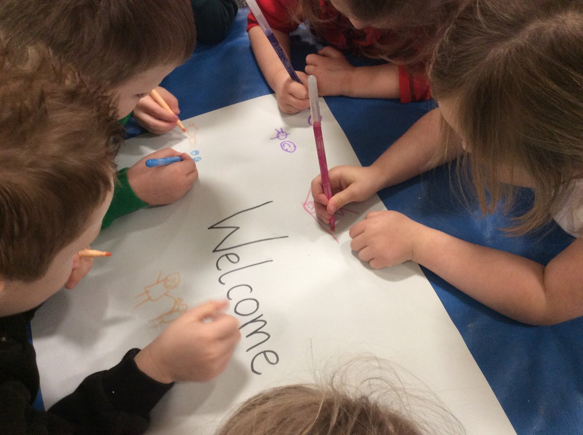 A group of children writing the word welcome on a piece of paper